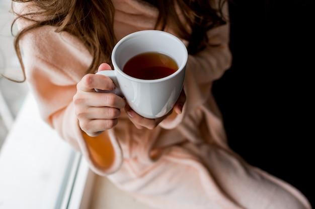 熱いお茶のカップを保持しているバスローブの女性。外気分。