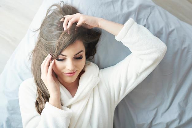 그녀의 침대에서 목욕 가운을 입은 여자
