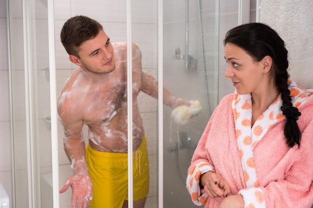 목욕 가운을 입은 여성이 남편에게 현대적인 타일 욕실에 서서 샤워를 할 차례라고 지적합니다