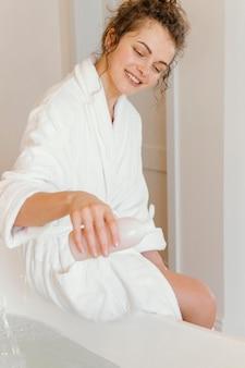 욕조에 비누를 붓는 목욕 가운에 여자