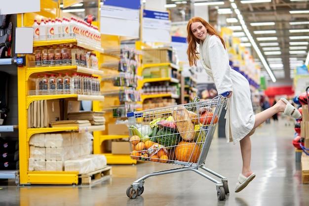 Женщина в халате, делая покупки в супермаркете, выбирая продукты, с тележкой. в рыночном проходе