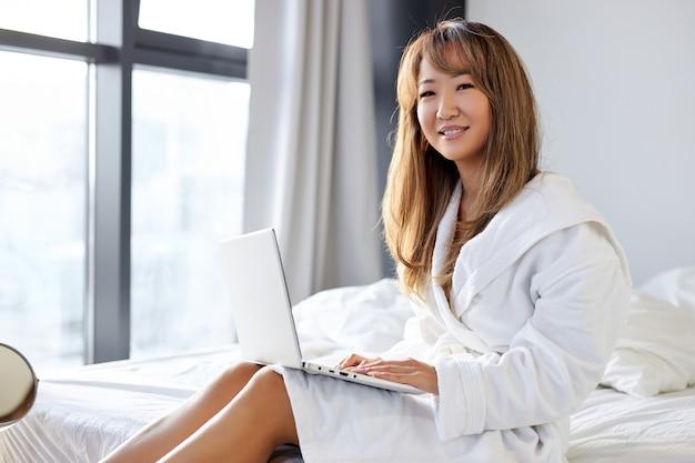広い白いベッドに座って、ラップトップで入力し、家で朝働いているバスローブを着た女性は、見た目も笑顔も。ライフスタイルのコンセプト