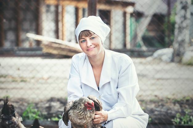 Женщина в халате улыбается молодой ветеринар проверяет кур на небольшой частной ферме