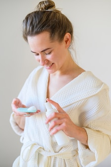 Женщина в халате с помощью лосьона