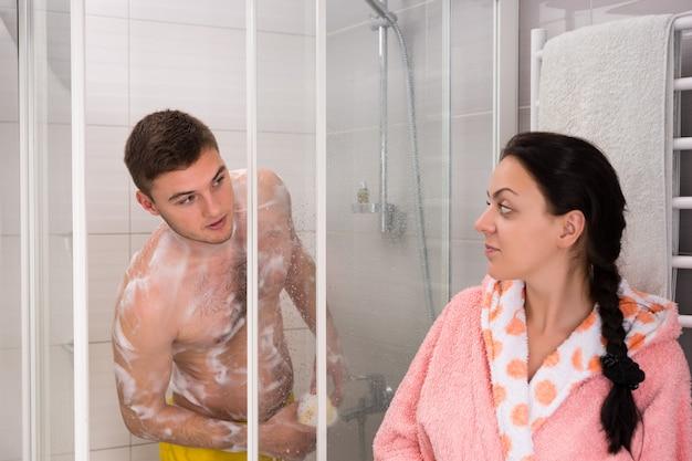 욕실에 투명한 유리문이 있는 샤워실에서 샤워를 하는 동안 밖을 내다보는 남자친구를 기다리는 목욕 가운을 입은 여성