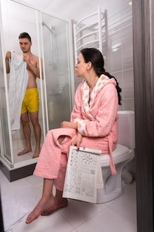화장실에 신문이 있는 목욕 가운을 입은 여성이 화장실에 투명한 유리문이 있는 샤워실에서 수건으로 닦는 동안 남자친구를 기다리고 있습니다.
