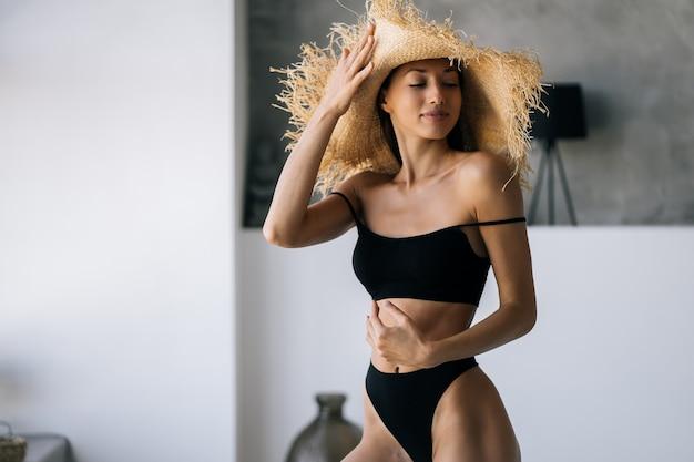 욕실에있는 여자. 밀짚 모자에 패션 초상화 모델입니다.