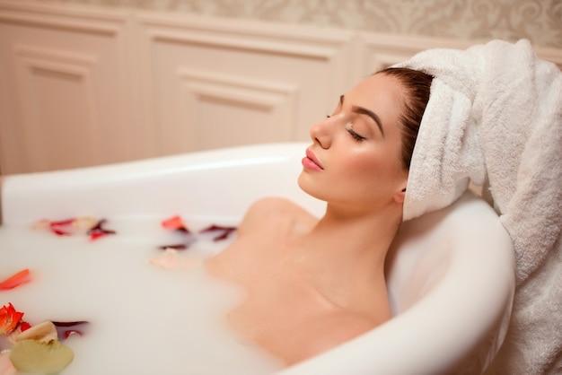 バラの花びらと泡のバスルームの女性。