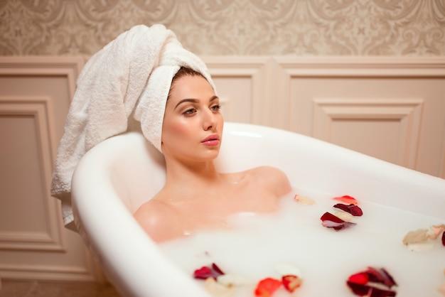 Женщина в ванной комнате с лепестками роз
