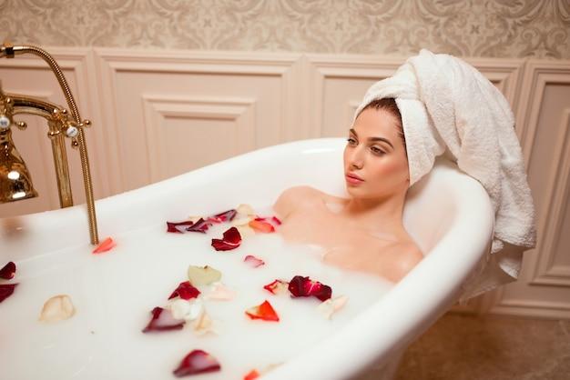 バラの花びらが付いている浴室の女性