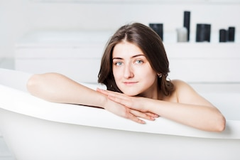 Woman in bathtub with hands on side