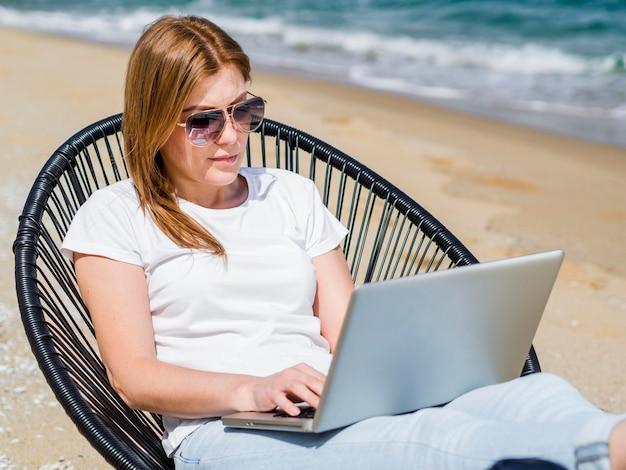 サングラスを着用しながらラップトップに取り組んでいるビーチチェアの女性