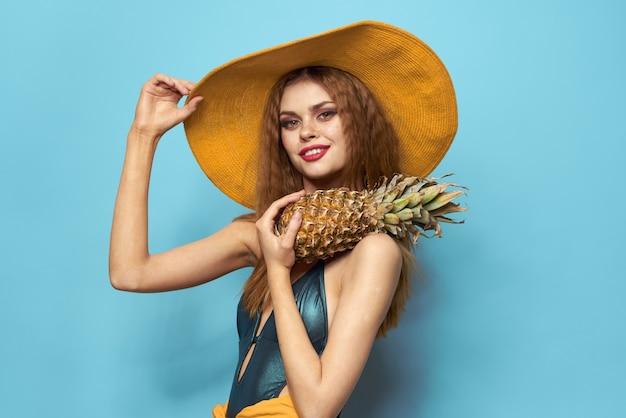 水着のエキゾチックな果物を保持しているビーチ帽子パイナップルの女性