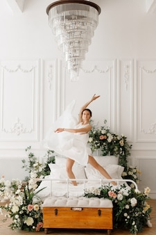 빈티지 홀에서 침대에 아름다운 하얀 드레스를 입은 여자 춤