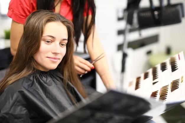 美容院の女性がカタログから白髪染めを選ぶ