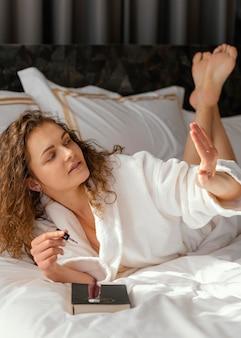 Женщина в постели, применяя лак для ногтей