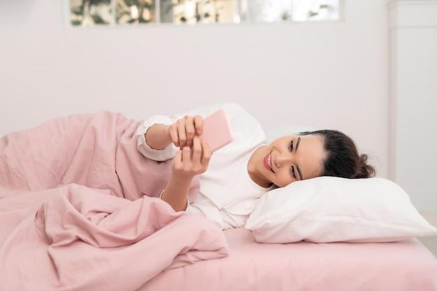 スマートフォンでソーシャルアプリをチェックするベッドの女性