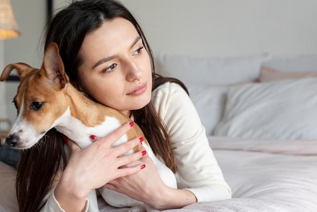Женщина в постели позирует со своей собакой