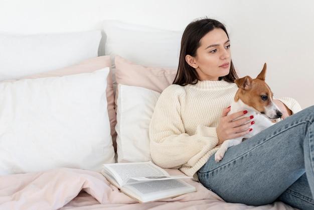 Женщина в постели отдыхает со своей собакой