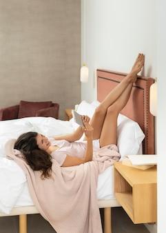 Женщина в постели с помощью планшета
