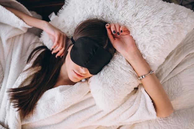 수면 마스크를 착용하는 침대에서 여자