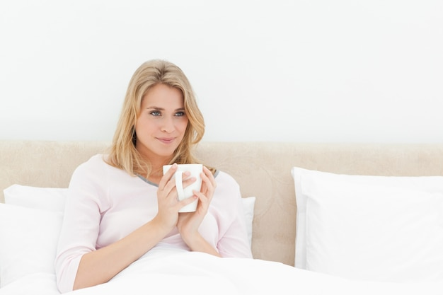 약간 측면을 보면서 부드럽게 웃 고 손에 컵 침대에서 여자