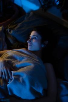 不思議な寝室のライトとベッドの中で女性