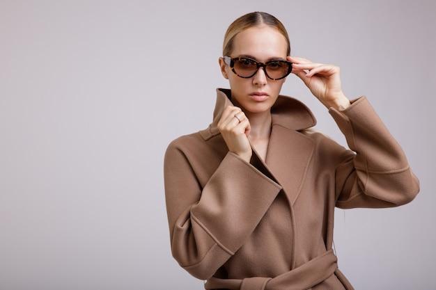 흰색 배경 스튜디오 샷 슬림 그림에 베이지색 갈색 가을 코트 세련된 선글라스 여자