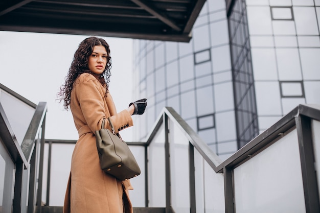 街を歩くベージュのコートを着た女性