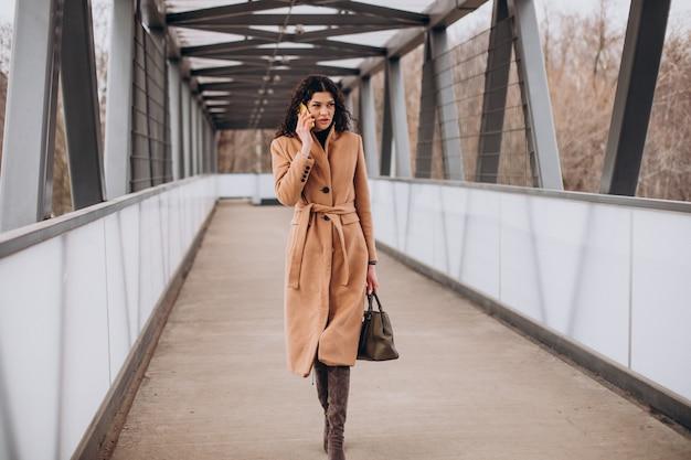 Женщина в бежевом пальто гуляет по городу