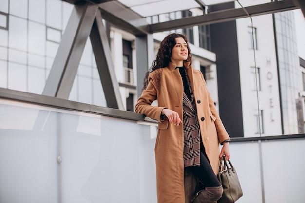 도시에서 걷는 베이지 색 코트에 여자