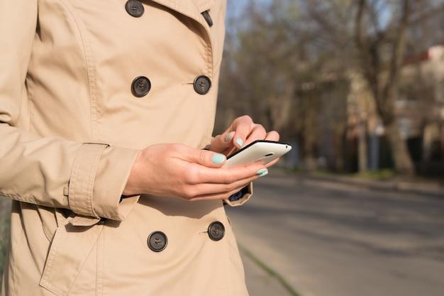 Женщина в бежевом пальто с ярким маникюром с помощью мобильного телефона на открытом воздухе