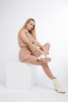 Женщина в бежевых брюках костюма мокрые сапоги на белом фоне модель сидит на кубе блондинка