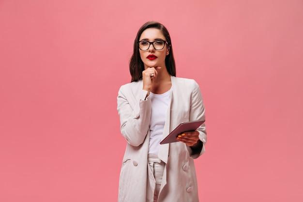 ベージュのスーツを着た女性が思慮深くポーズをとり、タブレットを持っています。軽いファッショナブルな服装とメガネの真面目な女の子がカメラにポーズをとる。