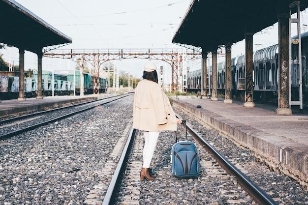 기차역에서 기차를 기다리는 베레모와 베이지 색 재킷에 여자.