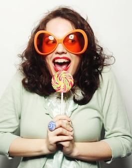 彼女の舌でロリポップを舐めている大きなオレンジ色のメガネの女性