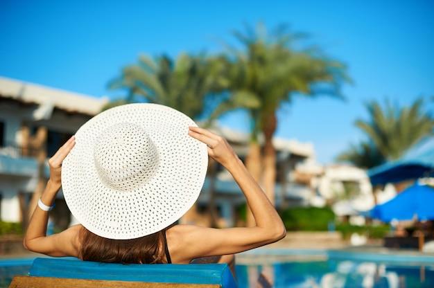 ホテルのスイミングプールのそばのラウンジャーで横になっている大きな白い帽子の女性、旅行する夏の概念