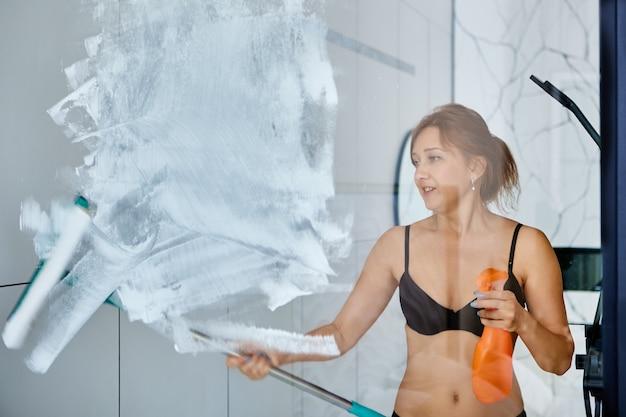 ビキニの女性がモップとスプレーでバスルームのガラスをきれいにする