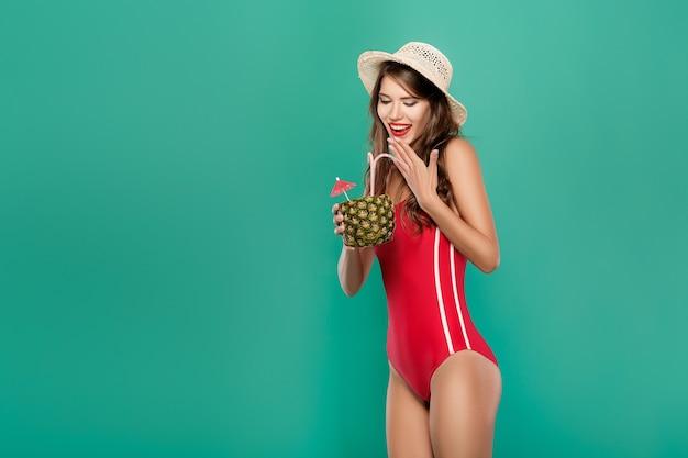비키니 입은 여자는 파인애플에 여름 칵테일을 마신다