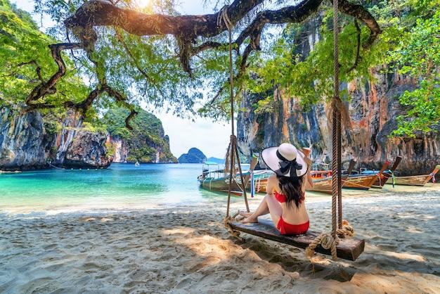 태국 크라비 코 라오 라딩 섬에서 비키니를 입은 여성이 그네에서 휴식을 취합니다.