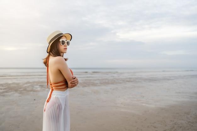 海のビーチで腕を組んで立っているビキニの女性