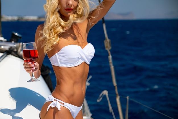 夏のカタマランセーリングクルーズでビキニの日焼けとリラックスしたワインを飲む女性