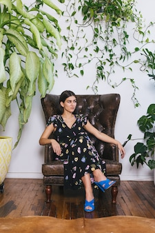 茶色のソファに座っている黒と白の花柄のドレスを着た女性