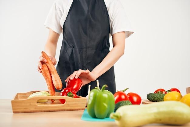 Женщина в черном фартуке приготовление здоровой еды изолированной предпосылкой. фото высокого качества