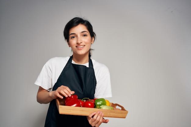 自宅で黒いエプロンキッチン野菜健康食品の女性