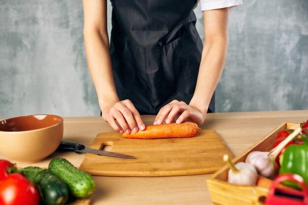 집에서 검은 앞치마 점심 식사를 하는 여성 채식 음식 도마