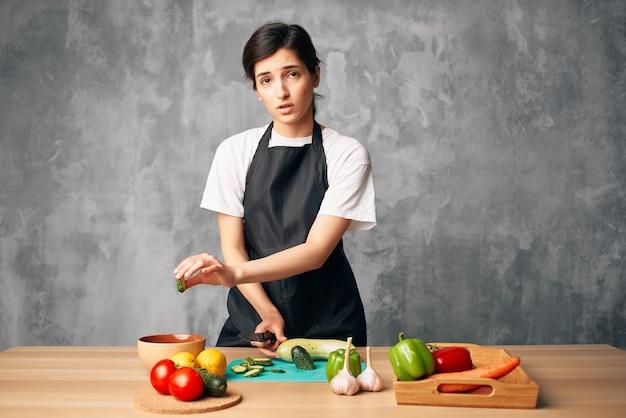 Женщина в черном фартуке обедает дома вегетарианская еда изолированный фон