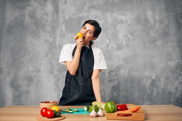 Женщина в черном фартуке на кухне резки овощей изолированного фона. фото высокого качества