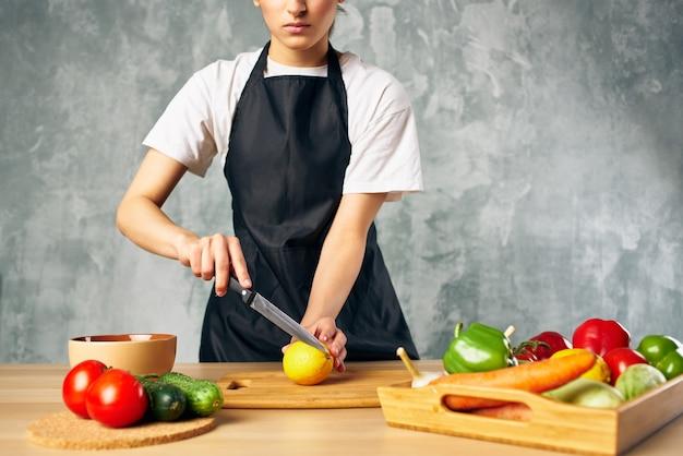 野菜を切る台所の黒いエプロンの女性は、背景を分離しました