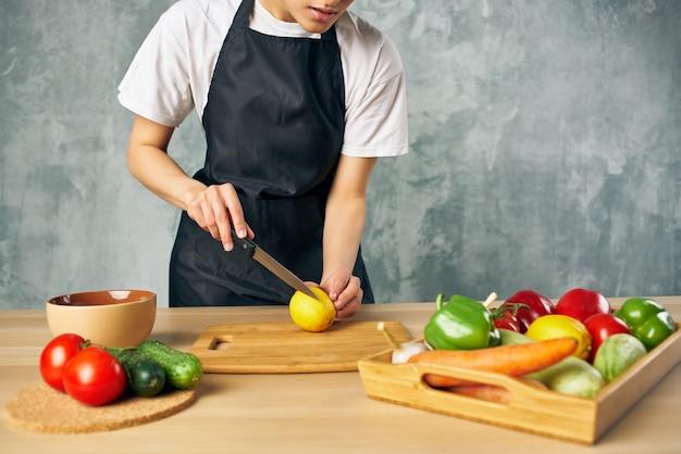 野菜の孤立した背景を切る台所の黒いエプロンの女性